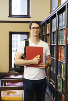 Portrait of confident male student with backpack holding book while standing by shelf in library