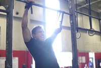 Aggressive male adaptive athlete screaming while doing chin-ups in gym