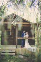 Portrait of newlywed couple standing in porch at forest 11100111038| 写真素材・ストックフォト・画像・イラスト素材|アマナイメージズ