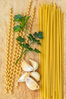 Pasta, parsley, and garlic on wooden board