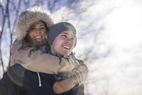 Young woman with arms around man during winter outdoors