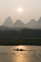 Tourist boat sailing through karst scenery at sunrise on the Li river (Lijiang) in Yangshuo, near Guilin, Guangxi Province 11104008437| 写真素材・ストックフォト・画像・イラスト素材|アマナイメージズ