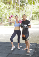 Young woman wearing pink boxing gloves with her trainer