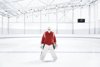 Ice hockey goalkeeper wearing red uniform at an ice rink