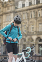 Woman adjusting backpack as she prepares to commute by bicycle 11107007217| 写真素材・ストックフォト・画像・イラスト素材|アマナイメージズ