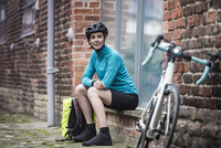 Female cyclist sitting by bicycle on brick wall 11107007229| 写真素材・ストックフォト・画像・イラスト素材|アマナイメージズ