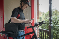 Mature man with bicycle checking smartphone at front door 11107007234| 写真素材・ストックフォト・画像・イラスト素材|アマナイメージズ