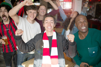 Football fans cheering at bar