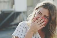 Young Woman Laughing While Hiding Mouth With Hand 11115000084| 写真素材・ストックフォト・画像・イラスト素材|アマナイメージズ