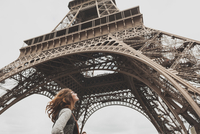Low Angle View Of Woman Standing In Front Of Eiffel Tower 11115000544| 写真素材・ストックフォト・画像・イラスト素材|アマナイメージズ