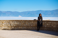 Full Length Of Woman Leaning On Retaining Wall By Mountains Against Clear Blue Sky 11115000928| 写真素材・ストックフォト・画像・イラスト素材|アマナイメージズ