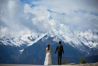Couple Standing In Front Of Snowcapped Mountains Against Cloudy Sky 11115000935| 写真素材・ストックフォト・画像・イラスト素材|アマナイメージズ