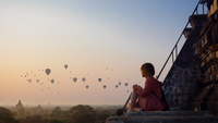 Woman Sitting On Stairway While Looking At Hot Air Balloons Against Sky During Sunset 11115001598| 写真素材・ストックフォト・画像・イラスト素材|アマナイメージズ