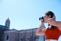 Low Angle View Of Beautiful Woman Photographing By Church Against Clear Sky 11115002369| 写真素材・ストックフォト・画像・イラスト素材|アマナイメージズ