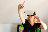 Middle-aged Woman Looking Through Virtual Reality Glasses 11115004818| 写真素材・ストックフォト・画像・イラスト素材|アマナイメージズ