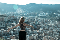 Woman Standing With Arms Outstretched By Cityscape And Mountains 11115005196| 写真素材・ストックフォト・画像・イラスト素材|アマナイメージズ
