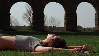 Young Woman Relaxing On Grassy Field Against Old Ruin 11115005381| 写真素材・ストックフォト・画像・イラスト素材|アマナイメージズ