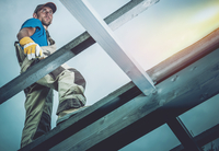 Low Angle View Of Worker Standing At Construction Site Against Clear Sky 11115005951| 写真素材・ストックフォト・画像・イラスト素材|アマナイメージズ