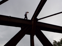 Low Angle View Of Man Standing On Metallic Structure At Construction Site Against Sky 11115006887| 写真素材・ストックフォト・画像・イラスト素材|アマナイメージズ