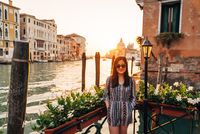 Portrait Of Woman Standing By Canal Against Santa Maria Della Salute 11115009366| 写真素材・ストックフォト・画像・イラスト素材|アマナイメージズ
