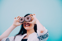 Low Angle View Of Smiling Young Woman Holding Donuts Against Clear Blue Sky 11115009387| 写真素材・ストックフォト・画像・イラスト素材|アマナイメージズ
