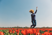 Woman Jumping In Field Against Clear Sky 11115010061| 写真素材・ストックフォト・画像・イラスト素材|アマナイメージズ