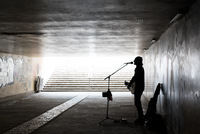 Silhouette Of Street Musician Playing Guitar While Singing At Underground Walkway
