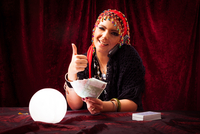 Portrait Of Smiling Female Fortune Teller Holding Money Showing Thumbs Up While Sitting With Tarot Cards And Crystal Ball At Tab