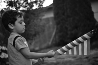 Side View Of Boy Holding American Flag While Standing In Yard 11115013509| 写真素材・ストックフォト・画像・イラスト素材|アマナイメージズ