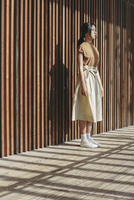 Full Length Of Young Woman Standing Against Wall 11115017565| 写真素材・ストックフォト・画像・イラスト素材|アマナイメージズ