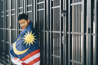 Side View Of Boy Wearing Malaysian Flag By Fence 11115020709| 写真素材・ストックフォト・画像・イラスト素材|アマナイメージズ