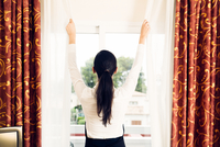 Rear View Of Woman Closing Curtain While Standing By Window 11115025440| 写真素材・ストックフォト・画像・イラスト素材|アマナイメージズ