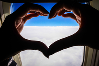 Close-up Of Hands Forming Heart Against Airplane Window 11115026585| 写真素材・ストックフォト・画像・イラスト素材|アマナイメージズ