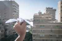 Cropped Hand Holding Paper Airplane Against Buildings