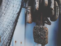 Close-up Of Fishing Net With Buoys By Wall 11115028728| 写真素材・ストックフォト・画像・イラスト素材|アマナイメージズ