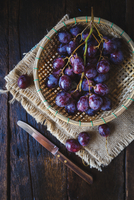 High Angle View Of Grapes In Wicker Basket By Knife On Wooden Table 11115029906| 写真素材・ストックフォト・画像・イラスト素材|アマナイメージズ