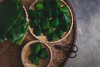 Directly Above View Of Rice Cakes Wrapped In Banana Leaves On Bamboo Tray 11115033836| 写真素材・ストックフォト・画像・イラスト素材|アマナイメージズ