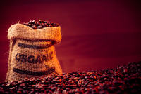 Close-up Of Roasted Coffee Beans With Sack Against Maroon Background 11115036714| 写真素材・ストックフォト・画像・イラスト素材|アマナイメージズ