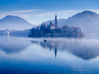 People Rowing Boat In Lake By Church And Mountains Against Sky During Foggy Weather 11115041442| 写真素材・ストックフォト・画像・イラスト素材|アマナイメージズ