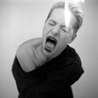 Young Woman With Blade On Tongue Screaming Against White Background