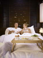 Smiling Couple Having Coffee While Relaxing On Bed In Hotel Room
