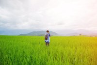 Woman Standing On Grassy Field Against Sky