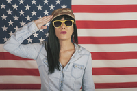 Portrait Of Beautiful Mature Woman Saluting While Wearing Sunglasses Against American Flag 11115063348| 写真素材・ストックフォト・画像・イラスト素材|アマナイメージズ