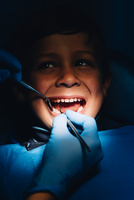 Dentist Operating Cheerful Boy In Medical Clinic