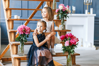 Siblings Sitting Amidst Flowers In Vase On Wooden Steps At Home