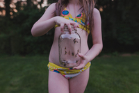 Midsection Of Girl Wearing Bikini Holding Insects In Jar While Standing Against Trees At Park 11115066420| 写真素材・ストックフォト・画像・イラスト素材|アマナイメージズ