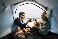 Son And Mother Toasting Coffee Cups While Sitting In Tent