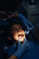 Dentist Operating Boy In Medical Clinic