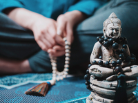 Close-up Of Buddha Figurine Against Woman With Beads Sitting On Carpet