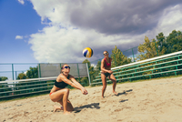Female Friends Playing Volleyball At Beach